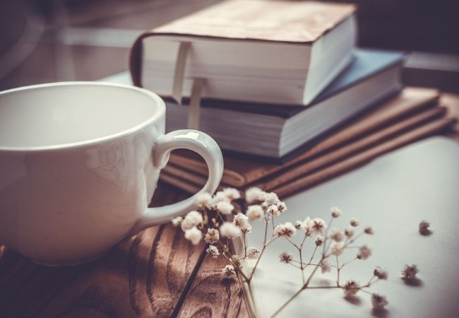 Stack of five vintage books with white mug and baby's breath