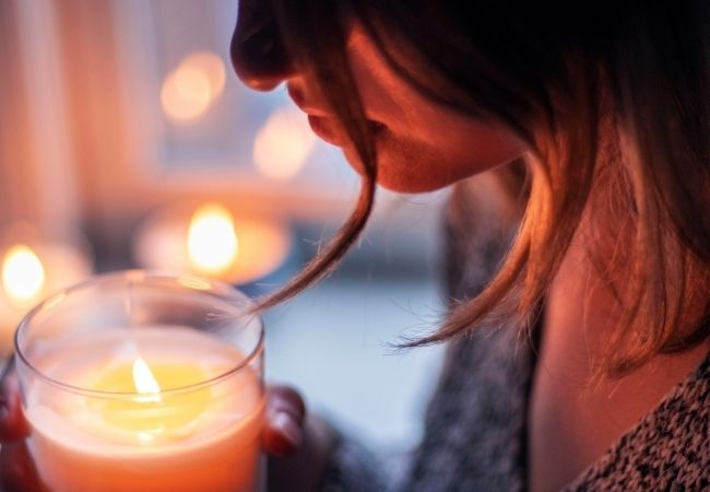 Woman holding a lit candle in her hands