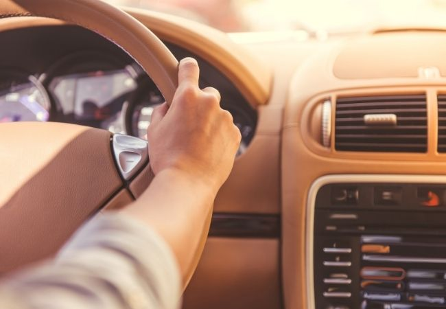 Woman's hands on a tan leather steering wheel