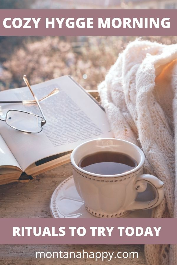 Book, glasses, tea, and blanket on a small table outside hygge morning