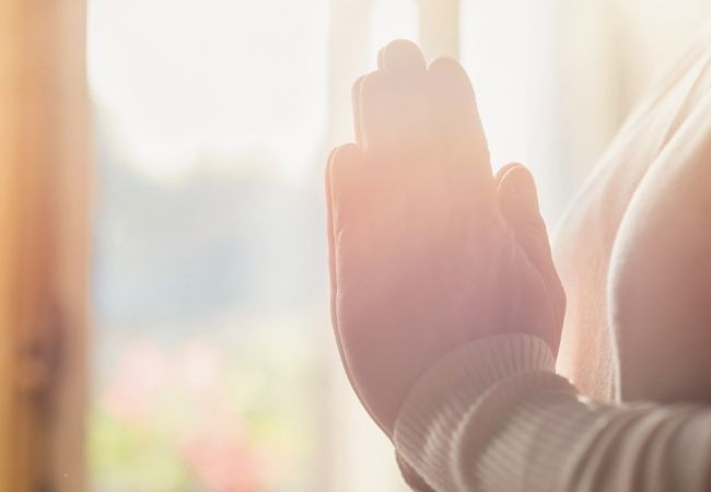 Praying hands in the morning light of a window - cozy hygge morning ritual