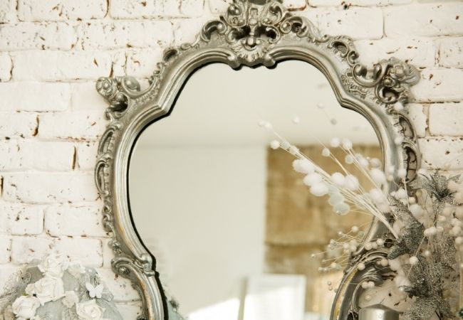 Ornate silver mirror against a white brick wall