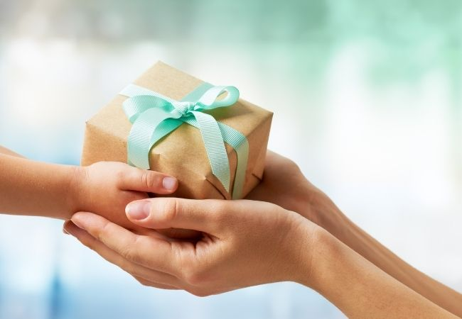 Close-up of a woman's hands handing a gift tied with a bow to a child's hands