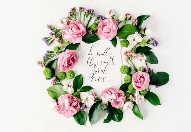 Quote Do small things with great love surrounded by flowers and leaves