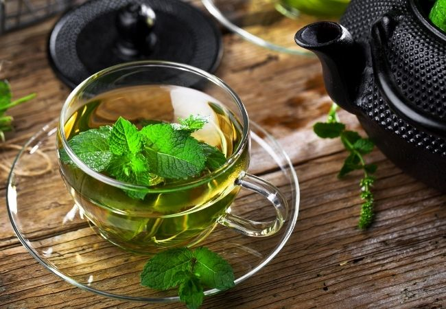 Cup of tea with peppermint leaves floating