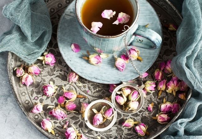 Large tray with teacup and dried rosebuds scattered on tray