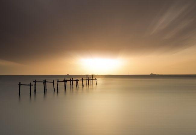 Minimalist photo of water, a bridge, and sunrise