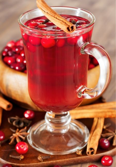 Clear Mug of Hot Cranberry Tea with a Cinnamon Stick with a bowl of fresh cranberries
