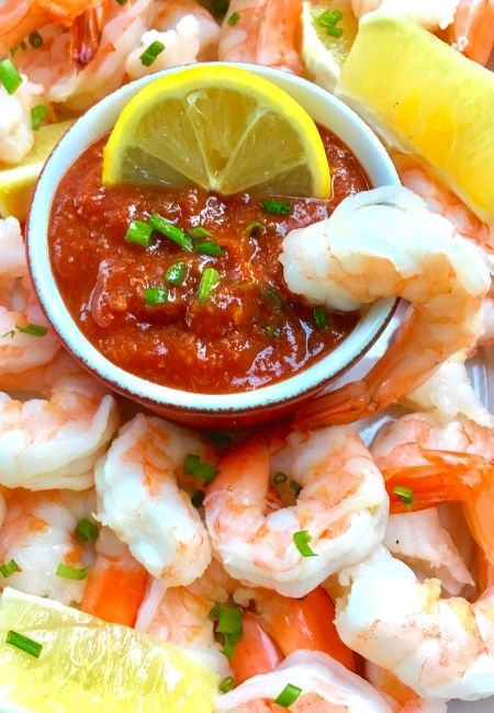 Close-up of how to make cocktail sauce for shrimp surrounded by shrimp with lemon and shrimp in the sauce.