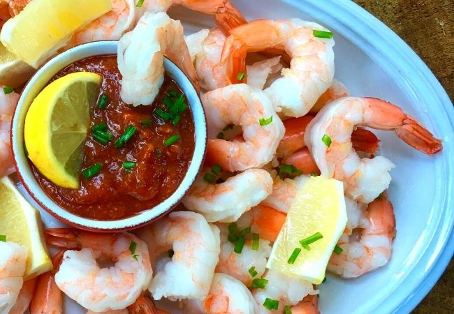 How to Make Cocktail Sauce recipe in a bowl surrounded by shrimp on a white platter.