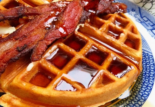 Close-up of Buttermilk Waffles with bacon and syrup on top