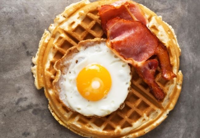 Large round waffle with a fried egg and Canadian bacon on top