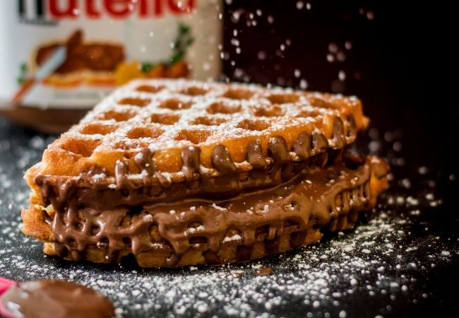 Waffle with Nutella spread between two layers and topped with powdered sugar