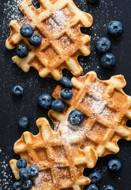 Three round waffles on a rustic background with fresh blueberries and powdered sugar