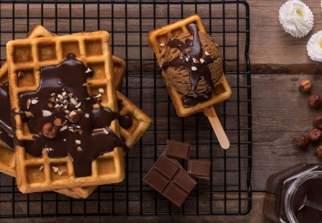 Waffles on a cooling rack with hot fudge sauce and chocolate ice cream