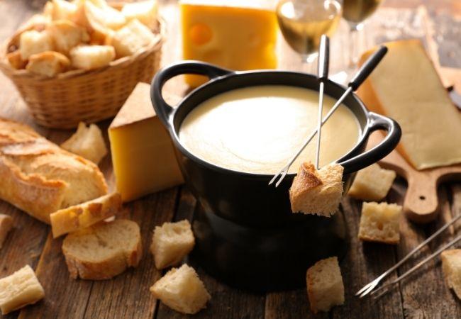 Cheese fondue pot with 1 inch cubes of bread and fondue forks