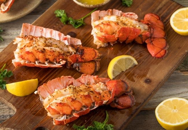 Cheese Fondue Dippers -cooked Lobster tails on a wooden cutting board with lemon wedges