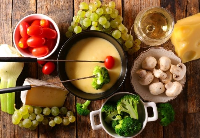 Cheese fondue dippers fresh vegetables - tomatoes, mushrooms, broccoli, fennel and pot of cheese fondue with grapes and a wedge of Swiss cheese