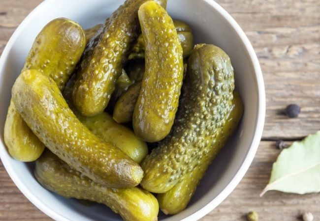 Cheese fondue dippers - pickles in a white bowl on a rustic background
