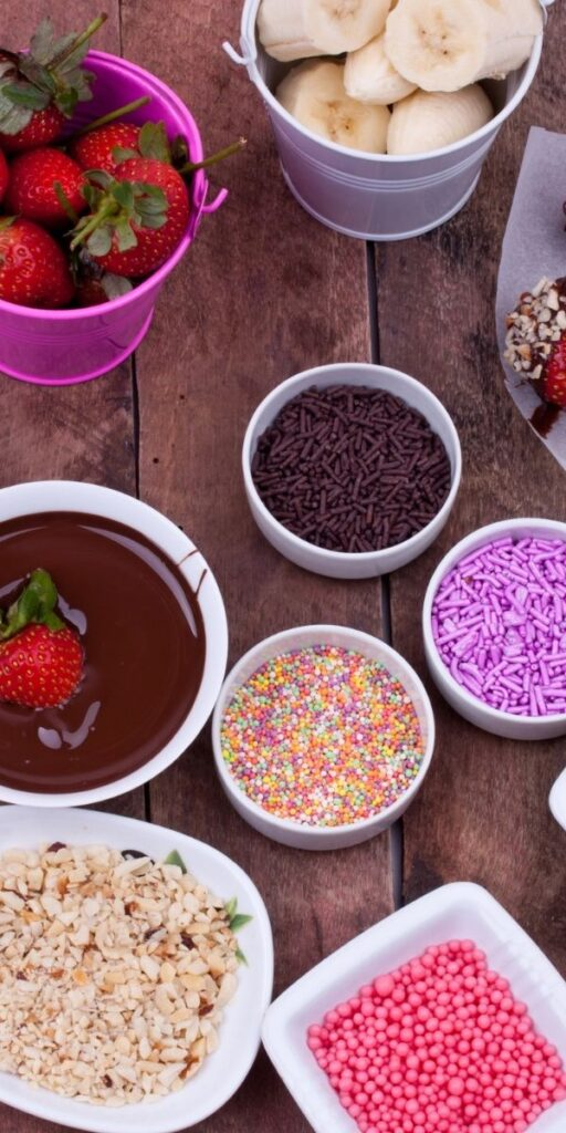 Overhead photo of chocolate fondue, crushed nuts and sprinkles in bowls, strawberries, and bananas