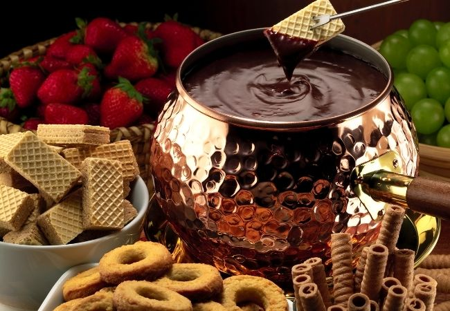 Copper fondue pot with chocolate fondue and an array of cookies to dip