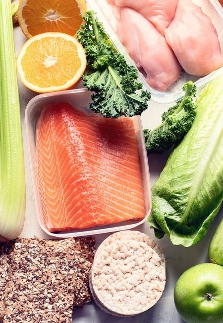 Container with raw salmon, raw chicken, celery, oranges, kale, lettuce, rice cakes - creative ways to save money