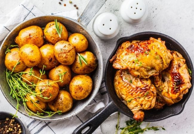 Cast Iron skillet with pan-fried chicken and a bowl of potatoes